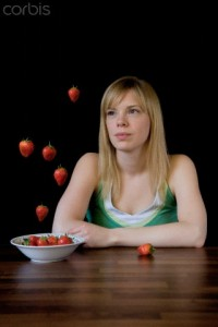 Young Woman Sitting at Table Looking at Strawberries Floating Mid-air