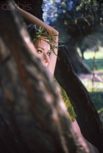 Young woman wearing crown of thorns and playing hide-and-seek in park, summer