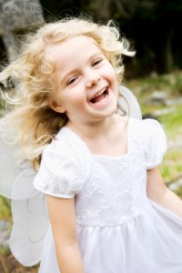 Little girl laughing dressed as fairy in churchyard