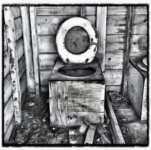 Dilapidated wooden toilet in outhouse