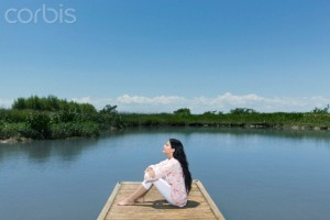 Woman relaxing on dock with eyes closed --- Image by © ZenShui/Corbis