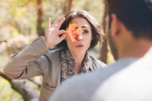 06 Oct 2014 --- Young woman holding autumn leaf over her eye in forest --- Image by © Chad Springer/Corbis