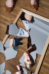 Woman Looking in Broken Mirror --- Image by © Turba/Corbis