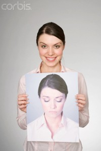 A woman holding a photograph of herself looking sad --- Image by © Image Source/Corbis