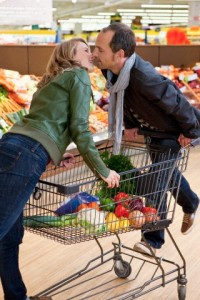 Couple kissing at shopping in supermarket --- Image by © Daniel Koebe/Corbis