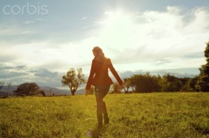 12 Sep 2013 --- Young woman in field walking away --- Image by © Manuela Larissegger/Corbis