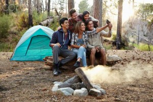 15 Oct 2014, Los Angeles, California, USA --- Four young adult friends taking smartphone selfie by campfire in forest, Los Angeles, California, USA --- Image by © Tony Garcia/Corbis